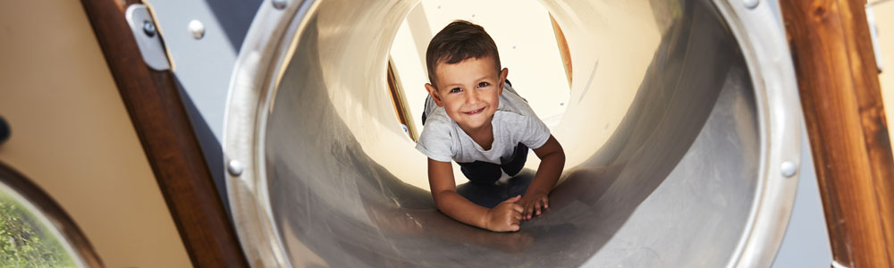 Boy crawling through a tunnel in an inclusive playground equipment